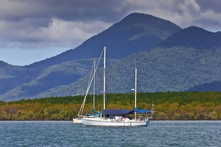 A sailing yacht with mountains in the background