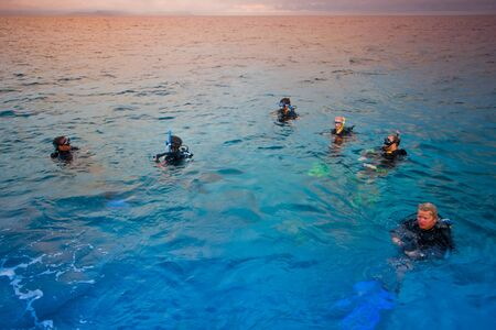 Men swimming in the sea with diving apparatus