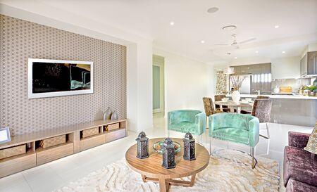Nowoczesne wnętrze domu z salonem z telewizorem i okrągłym drewnianym stołem z czarnymi lampami na wełnianym dywanie obok zielonego krzesła i jadalni obok kuchni