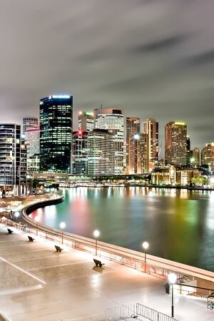 Sydney city and the river with lights illuminating on buildings under the  dark sky at night  from the opera house