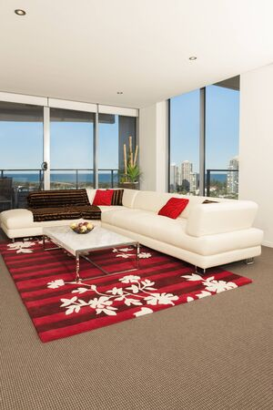 Image of a spacious living room with a white sofa, red carpet and big windows Stock Photo - 131204247
