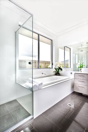 Luxury bathroom floor is made of shiny tiles. The bathing area is covered with glass panels that next to the white ceramic bath tub under the window. There are few towels against the mirror on the white wall