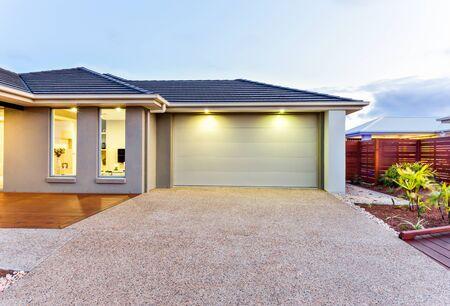 Parte de esta lujosa casa incluye un garaje con puerta blanca e iluminado por dos pequeñas luces debajo del techo.