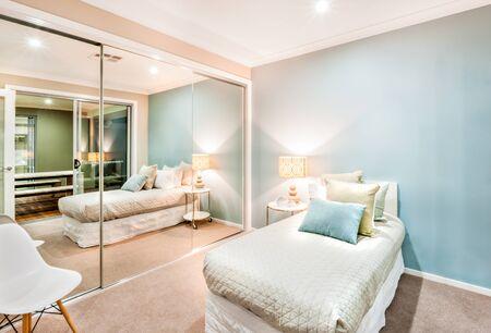 Moderne en klassieke slaapkamermuren zijn lichtblauw, verlicht met lampen en een tafellamp en één muur is volledig bedekt met grote spiegels. er staat een witte stoel erachter en bij het bed. de slechte heeft een dikke matras met kussens erop? Stockfoto