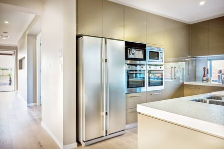 Neatly designed kitchen featuring a refrigerator, cabinets, a grill, and an oven 写真素材