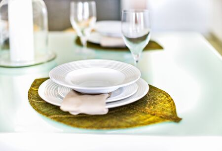 Closeup of a empty dish on green leaf shaped  decoration like braid, There are wine glasses near the it. Background is blurred. there are three dishes one on another.