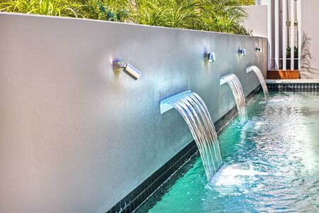 Modern wall-fountains on the side wall of a pool