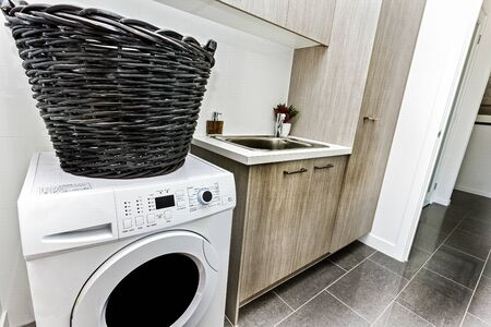Clean laundry area with front-load washing machine, a laundry basket, cabinets, and a basin