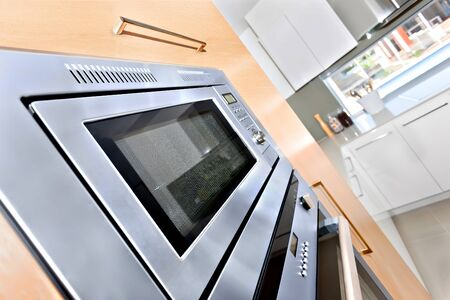 Silver color wall oven can see very clearly in the modern kitchen, there are pantry cupboards around the microwave oven that made by brown color wooden, There is a glass window and white color cabinet