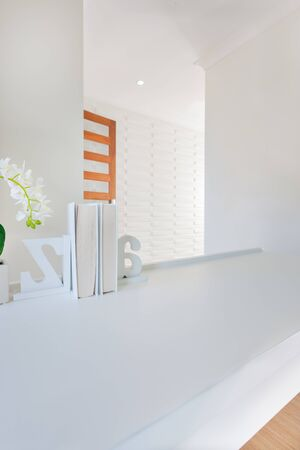 Top of the wooden surface of the table in a luxurious house, It has a white flower in the vase with an ornamental book shelf with 3d letters. Room walls are white and can be seen at the entrance or wa 写真素材
