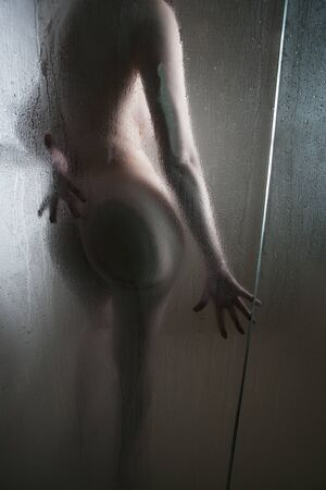 Sexy silhouette of a curvy woman in the shower seen through a glass door