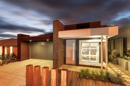 Eye-catching house view featuring a brick pattern wall, plantation, wooden flooring, and garage