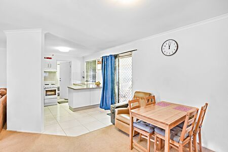 Dining room with wooden chair and table, comfortable furnitures with designs, walls are white color, pillows on chairs, inside rooms of a apartment. 写真素材