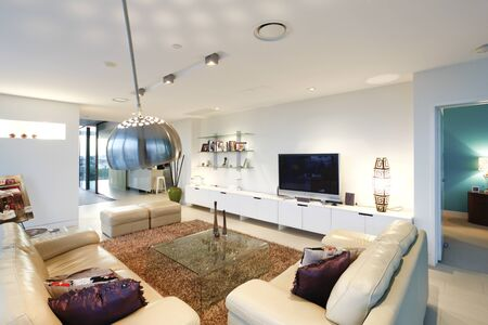 Television in living room near sofa set, comfortable furnitures and designs, walls are white color, chairs arround the tables, inside rooms of a apartment.