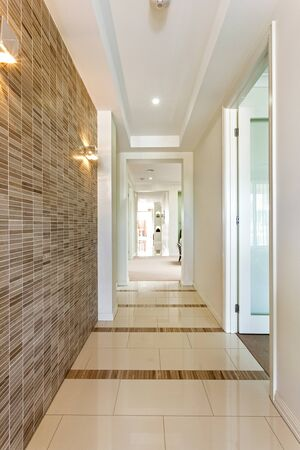 Modern corridor showcasing tiled flooring and wall, concealed ceiling lights, fire alarm, and  wall sconches