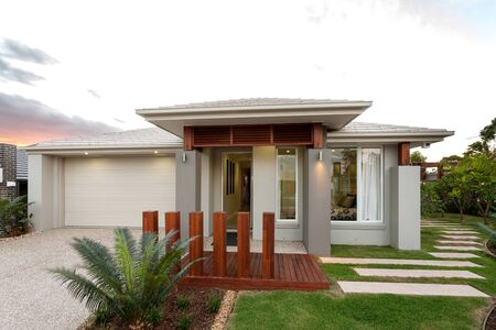 Designer house exterior with wooden passage, garage area, grass, plantation, and house entrance 写真素材