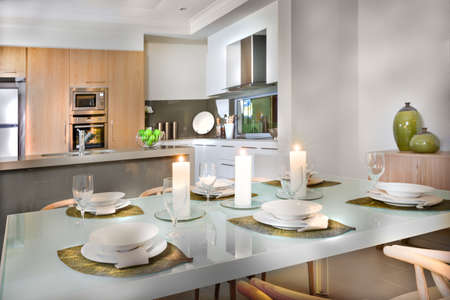 Shiny dining table ready to serve with dishes, wine glasses and flashing white candles. A leaf shaped braid is below the plates. The kitchen has wall oven, stove fixed next to the refrigerator, a faucet on the counter top table with fruits.