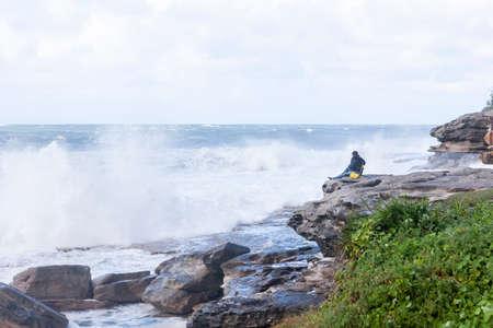 An unrecognizable person on the top of coastal rock watching storm waves crashing on the rocks, Bondi Australia. Stormy sea at bondi beach, Sydney, Australia
