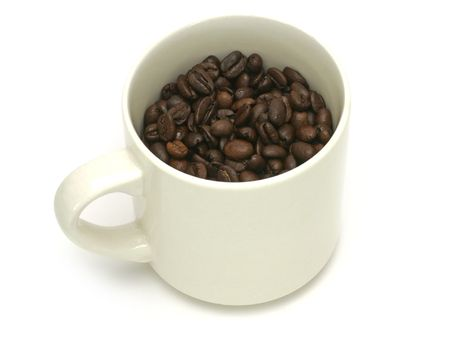 Studio isolated shot of coffee beans inside a typical white coffee mug