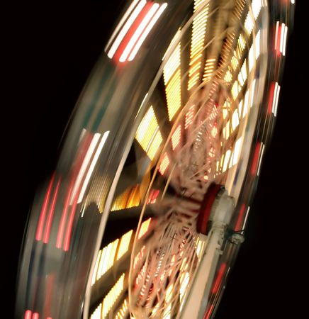 A Ferris Wheel blurred with motion, shot at night during a Carnival.
