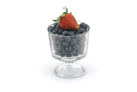 Bowl of organic blueberries and a strawberry