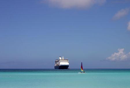 A cruise ship disembarks passengers via tender as others enjoy a relaxing sail in the beautiful Caribbean.