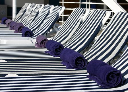 A great shot of a row of lounge chairs with folded towels on a cruise ship.  Stock Photo