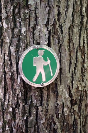 Close up of a hiking trail guide sign posted on a tree.  Stock Photo