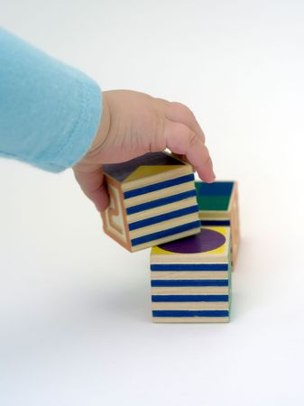 A toddler picks up blocks against a white background. Stock Photo