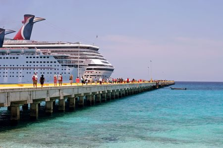 A pair of cruise ships are docked at the port in Costa Maya, Mexico in the Caribbean on a beautiful sunny day.