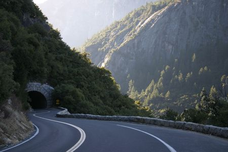 A great shot with mixed lighting of a road through mountains and a tunnel taken in route to Yosemite National Park in California. photo