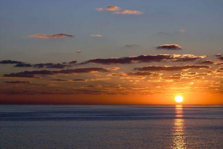 The sun sets against a clean ocean horizon in the Caribbean.