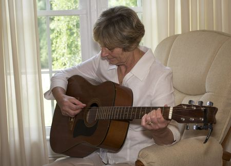 Close in shot of a senior woman playing guitar. Stock Photo