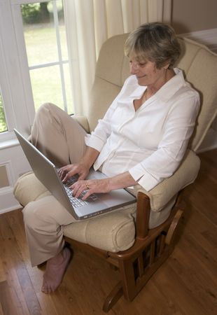 Close in shot of a senior woman using a laptop.
