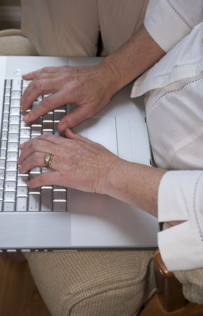 Close in shot of a senior woman typing on a laptop.