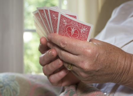 Close in shot of a senior woman holding a hand of playing cards.
