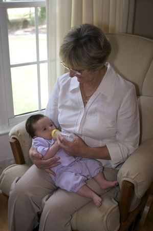 Close in shot of a grandmother feeding a bottle to a baby girl. Stock Photo