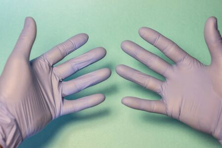hands with sanitary gloves over green field