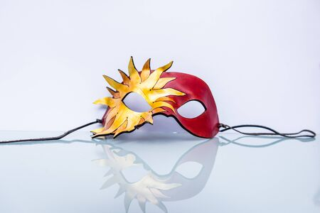 Venetian mask on white background with reflection in the lower half