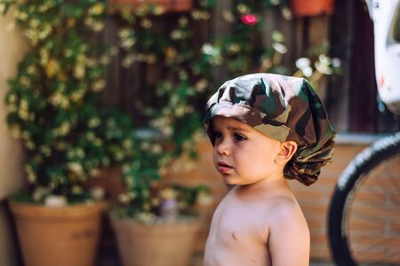 portrait of a child 18 months old wearing a hat and with the background out of focus.