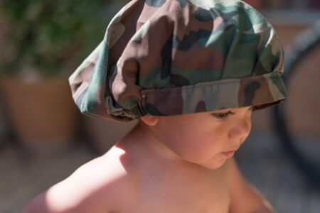 portrait of a child 18 months old wearing a hat and with the background out of focus. Stockfoto - 149879260