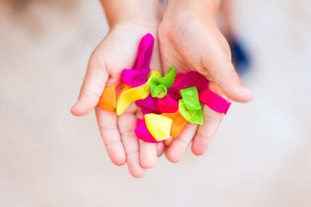 CHILD'S HANDS FULL OF SMALL COLORED BALLOONS Stockfoto - 155139535