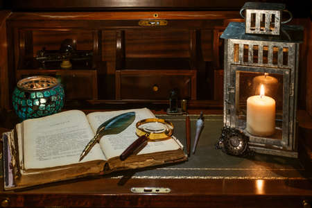 open book with candlelight, incorporates a camera, clock and a cup of coffee