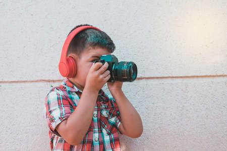 portrait kid listening to music with headphones on brick wall