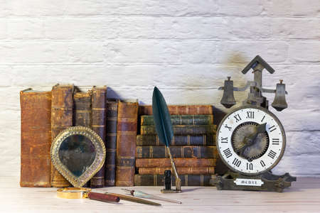 Antique watch along with antique books and vintage writing pen. 版權商用圖片