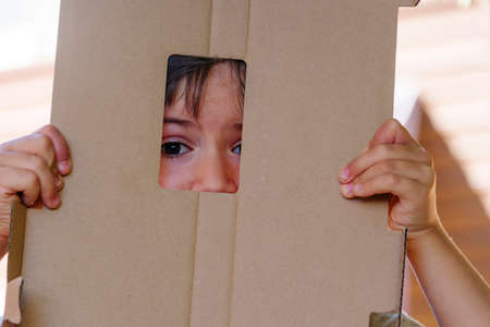 child hides in cardboard where only part of the face is visible