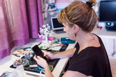 young woman in jewelry workshop writing a message on her cell phone