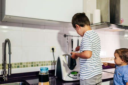 one kid preparing pancakes with a kitchen robot. Stockfoto
