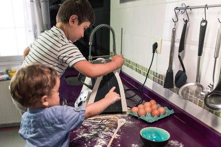Two children preparing pancakes with a kitchen robot. Stockfoto - 154936967