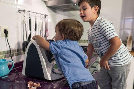 Two children preparing pancakes with a kitchen robot. Stockfoto - 154936897